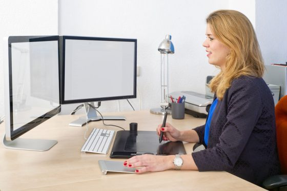 Woman working with dual monitors.